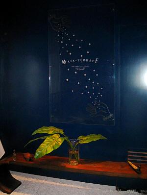 紺色の壁に、アクリルのお店の看板。白い星が左上から右下に流れるように描かれ、それを手のひらで受け止めている絵です。真ん中にMAYA-TERACE と白文字で書かれてあります。