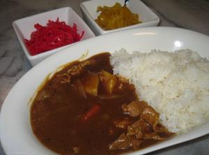 白いカレー皿に盛られたカレーライス。薬味は四角い白い器に、紅しょうがと、沢庵がそれぞれ盛られています。