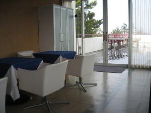 レストラン内部からテラス席を望む写真。白い椅子に白いテーブルクロス、そして紺色のクロスが二重に掛かっているテーブル。シンプルなレストランは、主役は外の星空ですと言っているようです。テラスは雨に濡れて椅子やテーブルは片端に積み上げられています。
