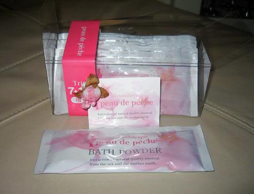 透明のケースに入った入浴剤。ピンクの(たぶん)桃の花が描かれており、全体にピンクがかっています。袋状のパッケージが7個入ったもの。peau de Peche BATH POWDER と書かれてあります。