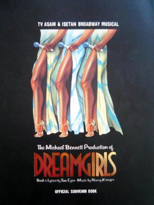 女性の下半身、スリットの深く開いた白いドレスから、すらりと伸びた左足が3本。足の付け根の部分にマイクを持った手が添えられているイラストが、真っ黒な表紙に描かれている公演プログラム。