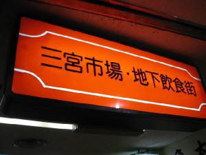 オレンジ色の通路の上によくある看板。三宮市場・地下飲食街と書かれてあります。