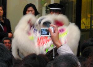 獅子舞に向かって片手を上げ、カメラで被写体を写そうとしている、そのカメラ越しに、獅子舞を狙って撮った写真。獅子舞の大きな顔の部分はぼやけ、カメラの中の獅子にピントが合っています。