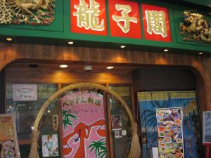 龍子閣と書かれたお店の入り口。写真入の大きなメニュー看板が入り口に置かれています。緑色の屋根に真っ赤なパネル、そこのお店の名前が金文字で書かれてあります。