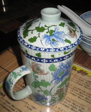 大きめの片手持ちのついたカップ。白地に青や赤の花が描かれた、オリエンタル風なカップです。