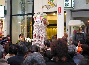 中国の獅子舞。白い身体に赤い模様がついています。沢山の人だかりが出来ていて、一際高く聳え立った後姿を撮った一枚。