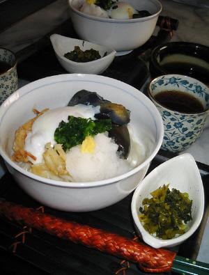 白い丼にうどん、小さな白い小鉢に高菜のお漬物、それらは竹細工の台の上に乗せられています。お茶の入った湯のみ茶碗が添えられてあります。