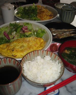 ご飯に味噌汁、手前に赤いお箸、向こうにたっぷりの野菜とオムレツが盛られた大皿、黒い丸いお皿にはししやもが。ご飯茶碗と同じ柄の湯飲み茶碗にはウーロン茶が入っています。