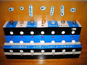 上段に各種金属のボールが置いてあり、下段には名前を伏せた丸いボールが置かれています。手で持って重さを計り、下段から正解を探し出す仕組み。