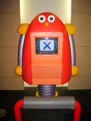 真っ赤なまん丸目玉のロボット。足は一本足です。胸に画面がついていて、どうやらクイズでも出しているようです。
