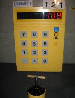 発電を計測するマシン。黄色い大きな電卓のような形をしています。数字が表示されるところには、前の人が残した108という数字が。本日の最高記録というところには、121という数字。