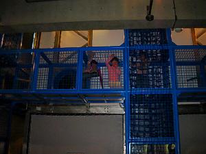 ブルーの網目のようなキューブをつなぎ合わせた縦横に入り組んだ通路。小さな子供たちが中に入って遊んでいます。