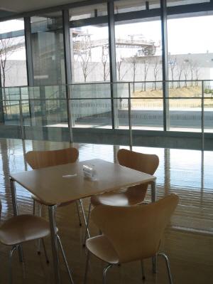 フローリングの床に白木のテーブルと椅子。大きく取られた窓から光がいっぱい差し込んで、明るいホールになっています。
