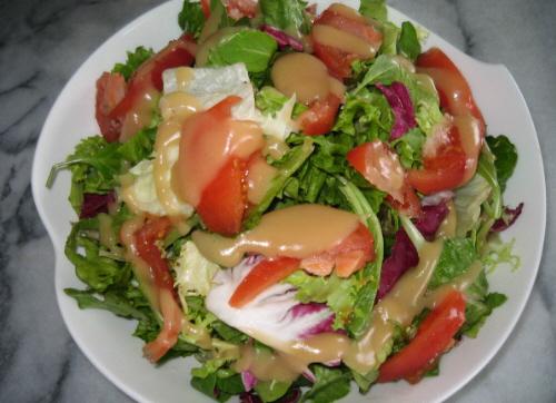 丸い大皿にたっぷりのサラダ。いろいろな葉とトマトが盛り込まれ、フォロのドレッシングがかけられてます。