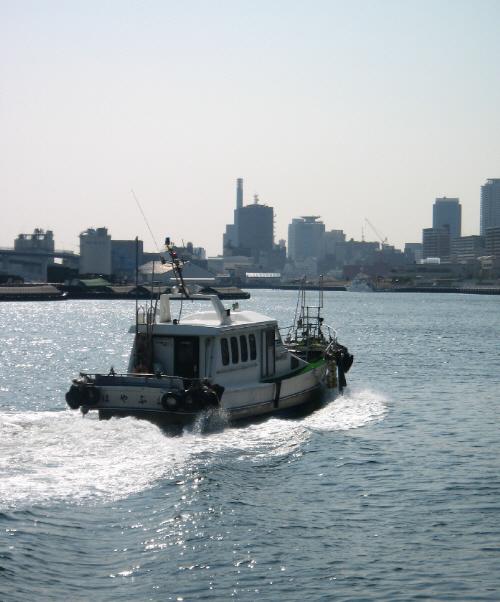 川のように見える入り江、でもここは海です。釣船が白い波を立てて走っています。船の向こう側に神戸市内の高いビル軍が見えています。