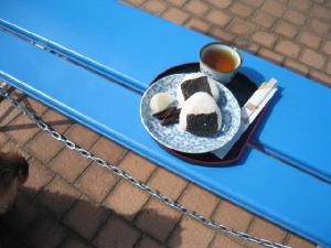 青いベンチの上に置かれたお盆、中にお握りの入ったお皿と、湯飲み茶碗、そして割り箸が。お握りには沢庵と佃煮が添えられています。