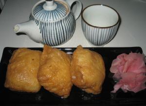黒い長方形のお皿に、大きめのおいなりさんが3つ、ガリがたっぷり添えられています。急須と湯飲み茶碗はお揃いの縦じま模様です。