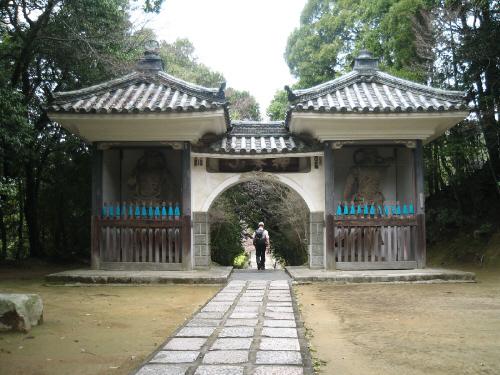 小さな塔のような形のものが左右に配置され、その真ん中は円形にくりぬかれた入り口がある、ちょっと中国っぽい形の参門。左右には仁王様がそれぞれ飾られています。