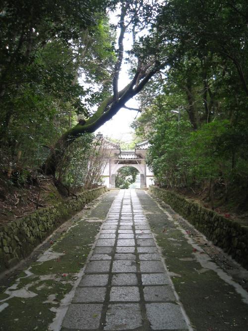 円形のアーチの山門を遠くに望む参道。両側を緑の木々が覆っていて、真ん中の石畳の直線が真っ直ぐに伸びて綺麗です。