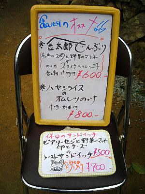 折りたたみいすの上に置かれたメニュー。おススメの文字の下に、金太郎どんぶり600円、ハヤシライスのオムレツのっけ800円と書かれてあります。その下に小さなメニューも置いてあり、本日のサンドイッチ500円との文字も。