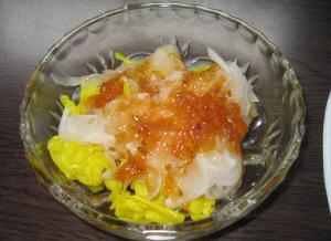 透明のガラスの器に、茹でた玉ねぎと黄色キャベツ、たっぷりの玉ねぎドレッシングがかかっています。