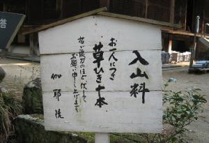 木の三角屋根の立て看板。白く塗られた上に黒い筆文字で、入山料・お一人につき草ひき十本。右ご協力のほど、伏してお願い申し上げます。と書かれてあります。