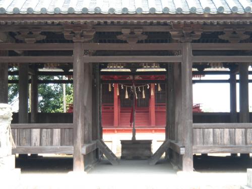 拝殿の入り口から本殿を望んだアップ画像。お賽銭箱と鈴が見えます。その奥に朱塗りの本殿が。