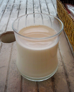 透明のグラスに注がれたミルク。白く塗られた木のテーブルの上に乗っています。