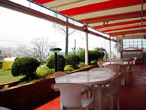 レストランのテラス。赤茶色の床に、赤と白のストライプの庇、テーブルや椅子は白です。テラスの外側の植木や芝生の緑が赤に映えて綺麗です。
