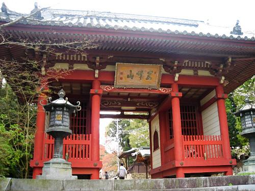 朱塗りの箱のようなものが左右に柱代わりになっており、その上に屋根がある、良く見かけるタイプの参門。看板には五峰山と書かれてあります。