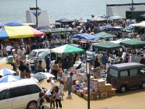 海がすぐ側のフリーマーケット会場。車やカラフルなテント、積み上げられたダンボール、行きかう人々、かなり賑わっている会場です。