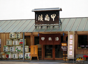 甲南漬と大きく書かれた看板の店構え。ここは高島忠雄の実家です。お店の入り口の脇には酒樽がピラミッド型に積んであります。