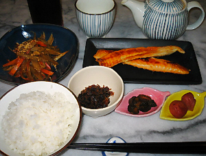 ご飯、ブルーの器にきんぴらごぼう、小さな白い丸の器に、昆布の振りかけ、葉っぱの形の小さな器に、梅干ときゅうりのきゅうちゃんがそれぞれ、長方形の黒いお皿にはらす、その向こうにはおそろいの縞模様の急須と湯飲み茶碗が。