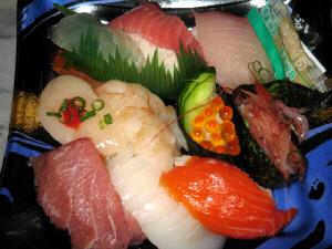 黒いトレイに入れられた握り寿司。中トロやサーモン、イカ、ホタテ、イクラ、ハマチなど、豪華なネタが揃っています。
