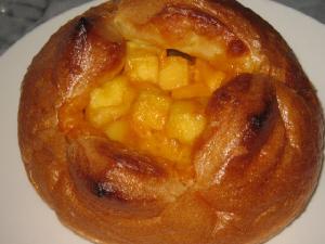 丸い大き目のパン。真ん中に十字に切込みが入れられたっぷりの角切りチーズが入っています。