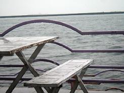 カフェの海の目の前の外側、ベンチとテーブルの向こうにはグレーの海が広がっています。雨に濡れたテーブルも何故か綺麗に見える海辺の景色です。