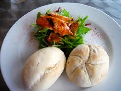 白い丸皿に小さめのパンがふたつと、サラダが盛り合わせてあります。サラダにはオレンジ色のドレッシングソースが。