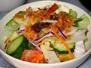 白い丸い器に盛られたサラダ。カラフルな色合いのサラダです。