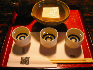 白いぐい飲みが3個、それぞれこちらの名品のお酒が3種類入っています。向こうの小鉢にはやはりここ手造りのお豆腐が。朱塗りのお盆で利き酒セットは提供されます。