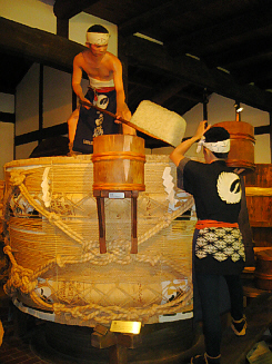 大きな樽の上に一人が乗り、下で小さな樽を持つ人。釜場での蒸米作業の様子が人形を使って再現されています。