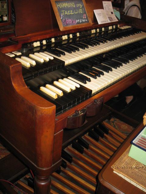 古い年代物のハモンドオルガンのアップ画像。譜面台の上にジャズライブのお知らせが書いた黒板が掲げられてありました。