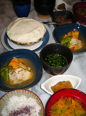 ゆっかりの降りかかったご飯、赤い塗り椀に味噌汁、その向こうに白い舟形の小鉢にザーサイが、四角い藍色の器に飛竜頭、その隣にお豆腐を浸ける出汁の入った小さめの黒っぽい深めの器、一番奥にザルに入った状態のお豆腐が置かれてあります。
