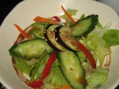 ここの名物、お漬物のサラダ。茄子やきゅうりのお漬物とレタスなどの生野菜が組み合わさり、あっさりしたお醤油ベースのドレッシングがかかっています。変形の白丸皿で。