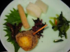 淡いグリーンのお皿に6種類のお漬物が盛られてあります。大根やみぶ菜、ごぼう等。