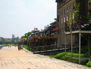 鴨川沿いの川の見える並びのお店には、大抵川床が設えてあり、多くの観光客が思い思いの場所でランチを楽しんでいます。川沿いの道は舗装され、家族連れやカップルがそぞろ歩きをしています。