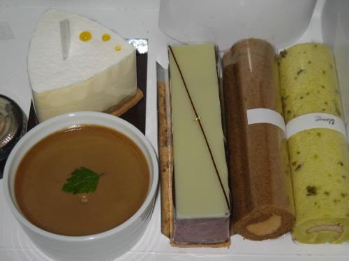 ケーキ3種類と、ミニロールケーキ2本の入ったケーキの箱。丸い白いカップに入っているのが栗のプリン、三角の形の白いケーキは、中にジャムが詰まっていました。細長い長方形のケーキは上のグリーンの色に似合わず、さくっとしたチョコケーキでした。ミニロールは、ピスタチオと、カカオ。ピスタチオが美味しかったです。