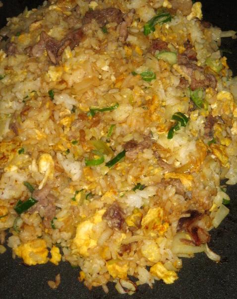 ホットプレートの上で調理された焼き飯のアップ画像。卵やネギなどの具材とご飯が混ざり合って美味しそうです。