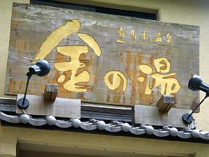 金の湯と書かれた看板のアップ画像。建物は新しくなっている金の湯ですが、この看板は古いものをそのまま使用しているようで、古い木の看板です。お湯の色や名前になぞらえて、文字の色は金色ですね。