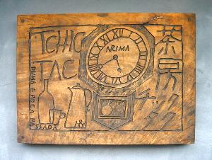 時計とお酒グラスが彫られた木の看板。茶房チクタクと書かれてあります。