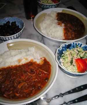 丸い和風っぽいお皿にハヤシライスが、その隣の和風の小鉢にきゅうりとツナのサラダが、赤いトマトがアクセントです。その向こうに漬物が並べられています。